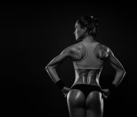 격리 된 검은 배경에 허리 근육과 손을 게재 체육 젊은 여자