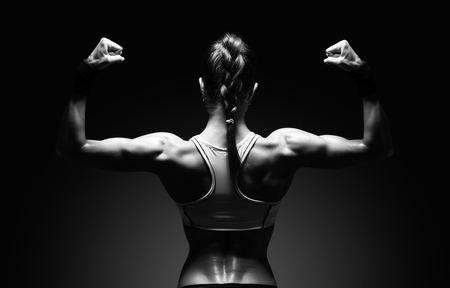 musculos: Mujer joven atlético que muestra los músculos de la espalda y las manos sobre un fondo negro aislado con trazado de recorte Foto de archivo