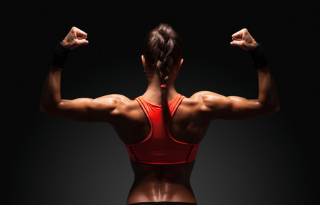 sports backgrounds: Athletic young woman showing muscles of the back and hands on a isolated black background with clipping path