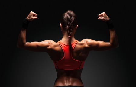 muscle: Mujer joven atl�tico que muestra los m�sculos de la espalda y las manos sobre un fondo negro aislado con trazado de recorte Foto de archivo