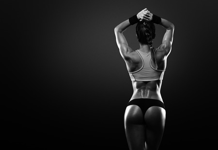 Mujer joven atlético que muestra los músculos de la espalda y las manos sobre un fondo negro aislado Foto de archivo - 36111598