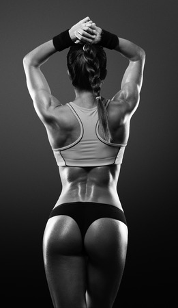 muscle girl: Athletic young woman showing muscles of the back and hands on a isolated black background