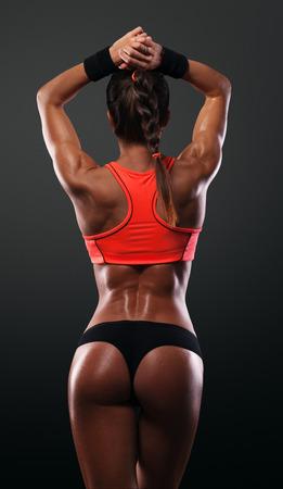 背中の筋肉を示す運動の若い女性と分離の黒い背景に手