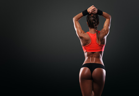 背中の筋肉を示す運動若い女性と手の分離された黒い背景に