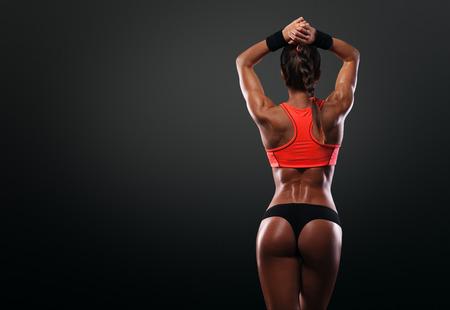 Atletische jonge vrouw toont spieren van de rug en handen op een geïsoleerde zwarte achtergrond