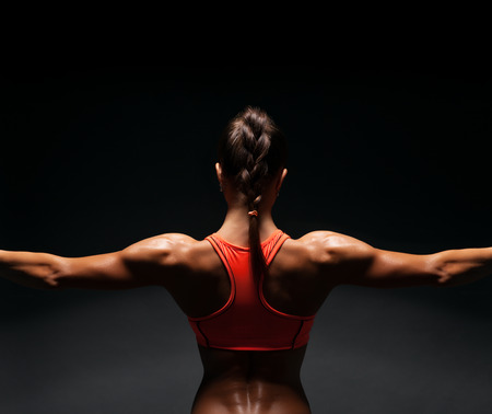 Athletic young woman showing muscles of the back and hands on a black background Stockfoto