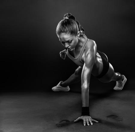 ejercicio aer�bico: Mujer joven que hace ejercicio-Ups Empuje la aptitud del entrenamiento del edificio del cuerpo postura ejercita en estudio