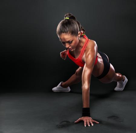 fitness: Junge Frau tun Push-ups Trainingseignung-Lage Bodybuilding übung auf Studio-