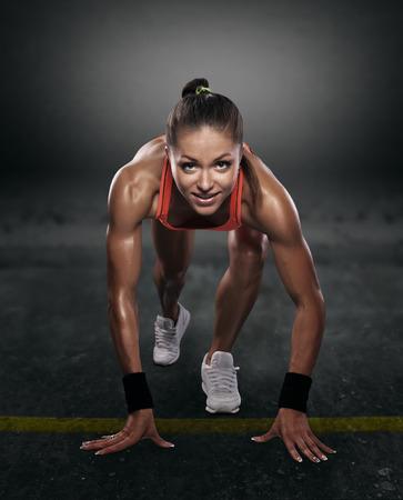mooie atleet op lage start op een donkere achtergrond geïsoleerd met het knippen van weg Stockfoto