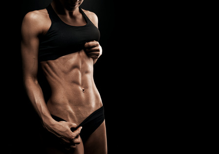 female bodybuilder: Beautiful athletic woman shakes her abdominal muscles on dark background