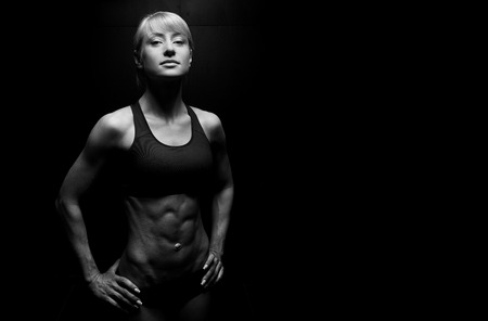 nice body: Portrait of a beautiful athletic woman on dark background Stock Photo