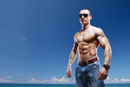 modelos hombres: chico en la playa con gafas de sol aislado con trazado de recorte Foto de archivo