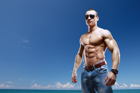 beach hunk: guy on the beach with sunglasses isolated with clipping path