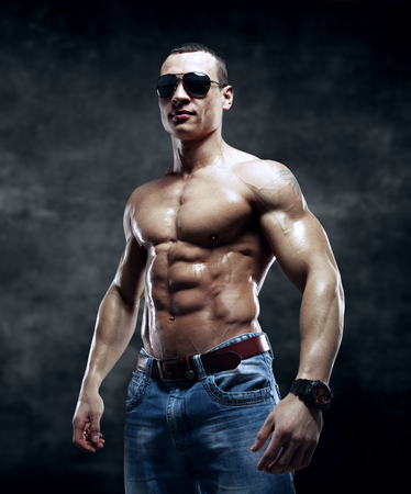 male model: guy on the dark background with sunglasses isolated with clipping path