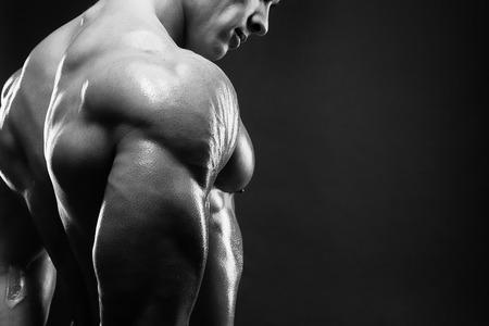 ginástica: Bodybuilder que mostra seu traseiro e bíceps, personal trainer. Homem forte que flexiona seus músculos