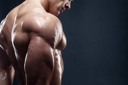 atleta: Bodybuilder que muestra su espalda y b�ceps m�sculos, entrenador f�sico personal. Hombre fuerte flexionando sus m�sculos Foto de archivo
