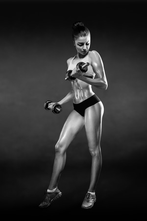 Fitness girl with dumbbells on a dark background isolated with clipping path Reklamní fotografie