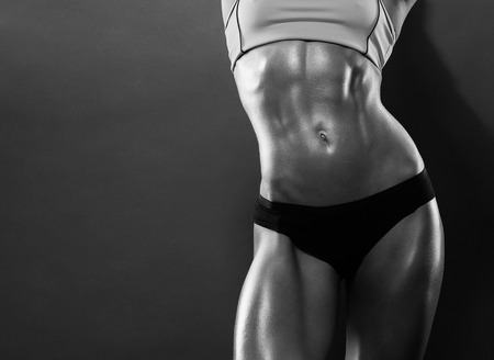 charming woman: Close-up of the abdominal muscles young athlete on gray background