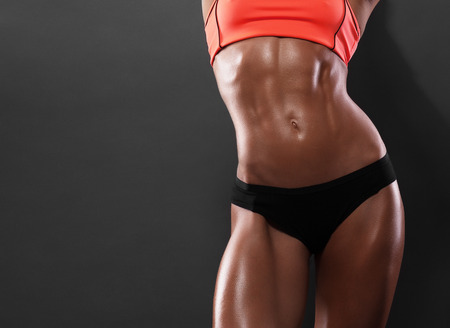an athlete: Close-up of the abdominal muscles young athlete on gray background