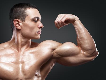 パワー フィットネス男の手のクローズ アップ。強いとハンサムな若いボディービルダーを示す彼の筋肉と上腕二頭筋
