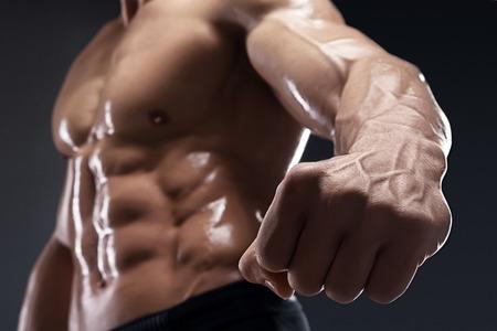 culturista: Culturista muscular hermoso muestra su puño y la vena, los vasos sanguíneos. Estudio tirado en el fondo oscuro. Foto de archivo