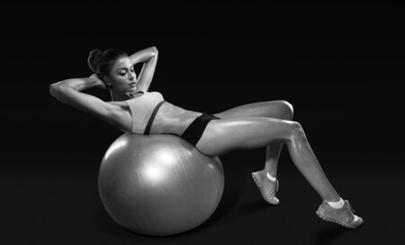 Fitness young woman doing abdominal crunch on fitness ball isolated with clipping path
