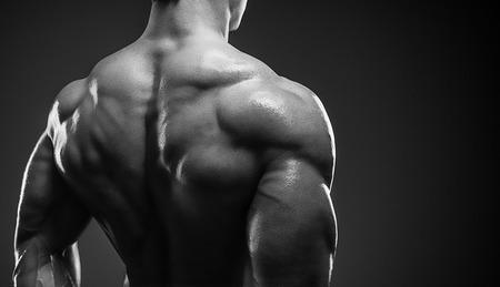 musculos: Bodybuilder que muestra su espalda y bíceps músculos, entrenador físico personal. Hombre fuerte flexionando sus músculos Foto de archivo