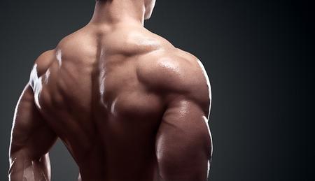 Bodybuilder die zijn rug en biceps spieren, persoonlijke fitness trainer. Sterke man buigen zijn spieren