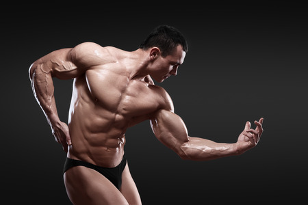 nude male body: Handsome muscular bodybuilder posing over black background. Isolated with clipping path. Stock Photo