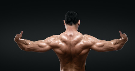 male muscles muscular pecs pectoral sexy young: Rear view of healthy muscular young man with his arms stretched out isolated on black background