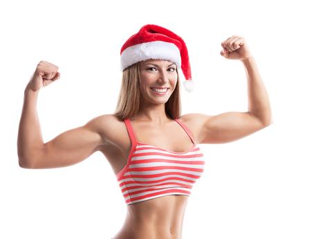 산타 모자를 입고 피트 니스 크리스마스 여자입니다. 행복 하 고 흥분 웃는 흰색 배경에 고립 된 밖으로 작동하는 여성 모델.