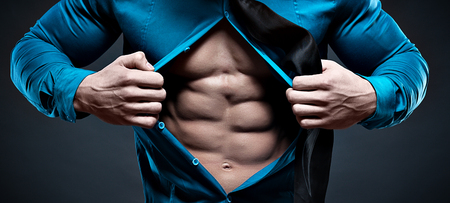 Young man displaying his abdominal muscles holding open his stylish blue shirt with his hands while looking  too camera Banco de Imagens - 46107513