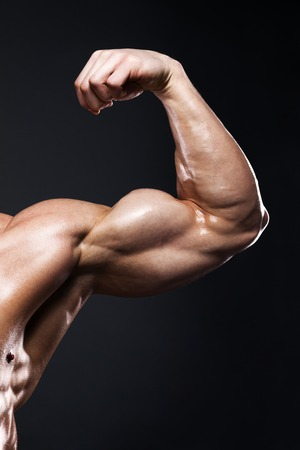 only the biceps: sport, bodybuilding, strength and people concept - close up of young man flexing and showing biceps over dark background with clipping path