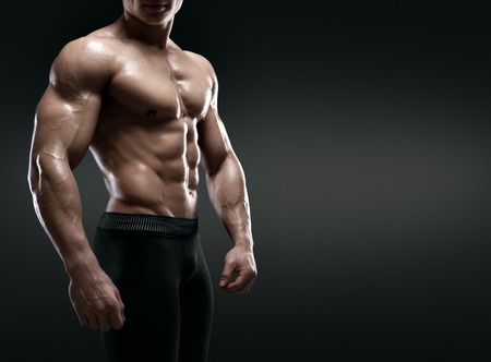 naked male body: Handsome muscular bodybuilder posing over black background. Isolated with clipping path. Stock Photo
