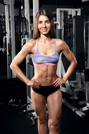 girl in sportswear: Beautiful smiling athletic woman at the gym. Attractive fitness woman, trained female body, lifestyle portrait, caucasian model Stock Photo
