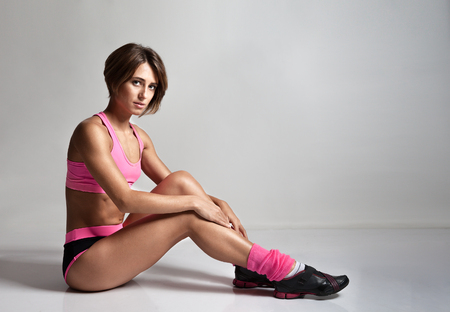 ankles sexy: Beautiful tried fitness woman sitting over floor after workout. Female fitness girl exercising indoor in fitness center. Beautiful fit caucasian model. Stock Photo