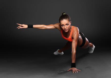 Jonge vrouw doet push-ups workout fitness houding body building oefening oefenen op studio