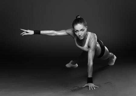 Mujer joven que hace ejercicio-Ups Empuje la aptitud del entrenamiento del edificio del cuerpo postura ejercita en estudio Foto de archivo - 50991223