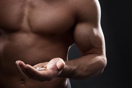 hombre fuerte: Primer plano de hombre musculoso torso con la mano llena de pastillas. Concepto de drogas, el dopaje, los esteroides anabólicos en el deporte.
