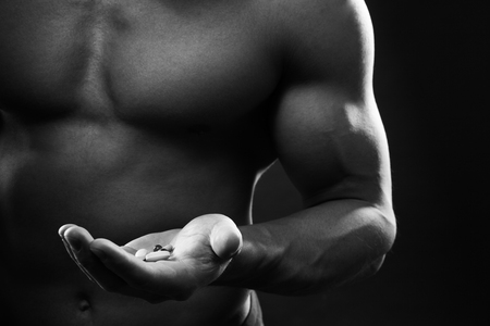 sixpacks: Close up of muscular man torso with hand full of pills. Concept of drugs, doping, anabolic steroids in sports. Stock Photo