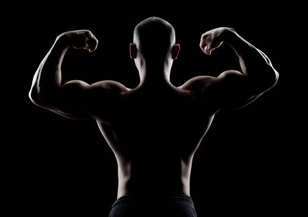 dorsi: bodybuilder demonstrates biceps on a dark background is over contrast. Confident young fitness  athlete man. Confident young fitness  athlete man. Back view.
