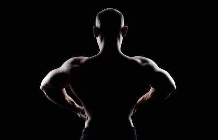 latissimus: Bodybuilder demonstrates latissimus dorsi on a dark background is over contrast.  Confident young fitness  athlete man. Back view. Stock Photo