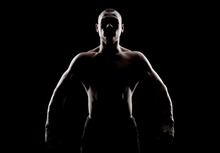 wrath: Silhouette of a strong fighter. Confident young fitness man with strong hands and clenched fists.