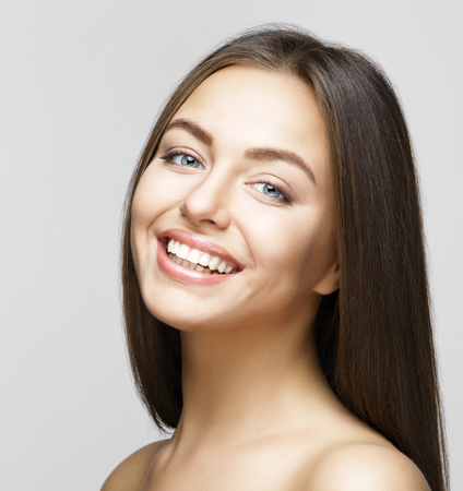 Portrait of attractive caucasian smiling woman brunette on gray background, studio shot toothy smile face long hair head and shoulders Stockfoto
