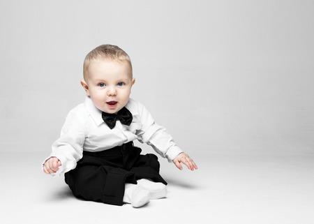 El bebé feliz. Niño pequeño en una camisa y pajarita blanca. Retrato de los niños. Hombre con estilo de moda en una corbata de lazo.