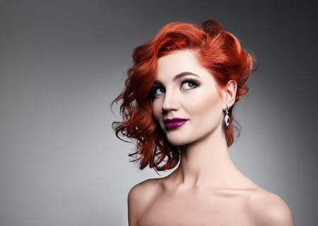 glamour model: Portrait of beautiful sexy girl with red hair styling and professional makeup. Luxury slender woman.