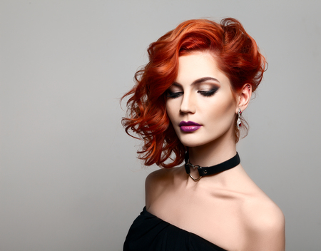 Beautiful model with curly red hair .  Styling hairstyles curls .Wavy shiny hair Imagens