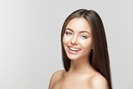 tooth whitening: Portrait of attractive caucasian smiling woman brunette on gray background, studio shot toothy smile face long hair head and shoulders Stock Photo