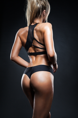 showing muscles: Athletic young woman showing muscles of the back and hands on black background Stock Photo