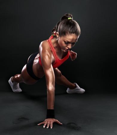 若い女性を行う腕立て伏せトレーニング フィットネス姿勢ボディ ビルディングの運動運動スタジオ
